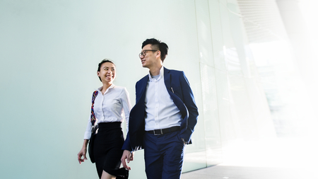 Asian business people in a discussion while walking