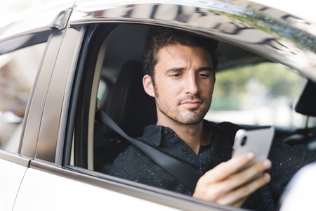 Man texting in his car Stock Photo