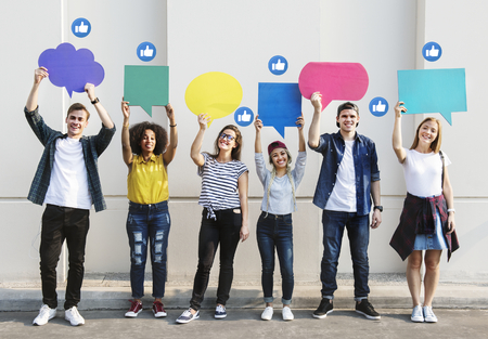 Young adults holding colorful speech bubbles