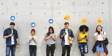 Glückliche Teenager, die süchtig nach ihren Smartphones sind Standard-Bild