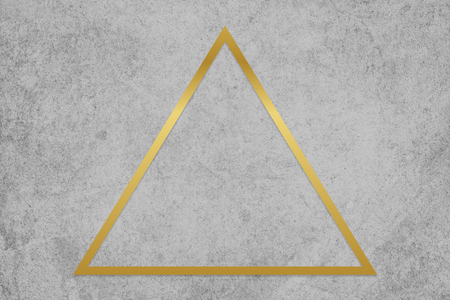 Gold triangle frame on a gray concrete textured background Stockfoto