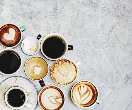 Assorted coffee cups on a textured background