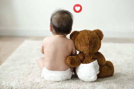 Niño sentado junto a su osito de peluche