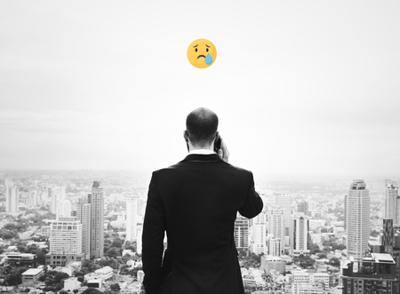 Emoji on a businessman talking on his phone overlooking the city