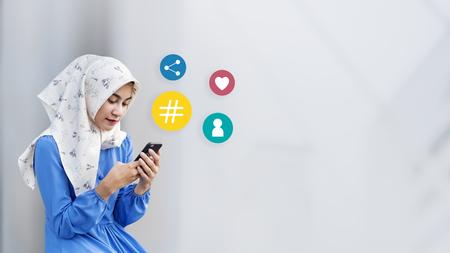 Muslim girl using her smartphone Stock Photo