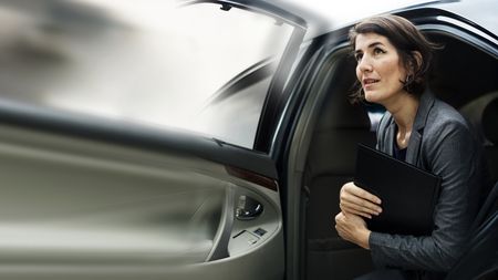 Businesswoman getting out from a car
