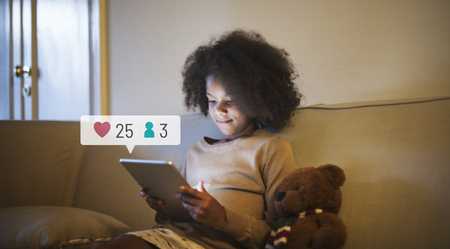 Young girl using a digital tablet before bedtime Stock Photo