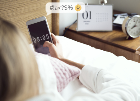 Woman checking her phone in bed