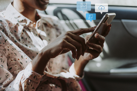 Woman using her phone in a car Stock Photo