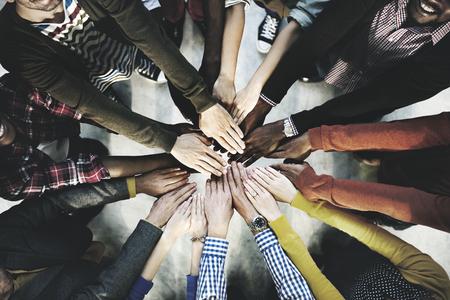 真ん中に手を積み重ねる多様な人々の空中写真