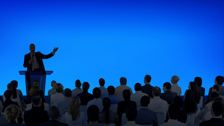 Corporate businessman giving a presentation to a large audience