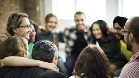 Happy people huddling in a room