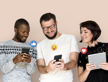Happy diverse people using digital devices Stock Photo