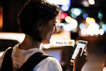 Happy woman texting while walking at night