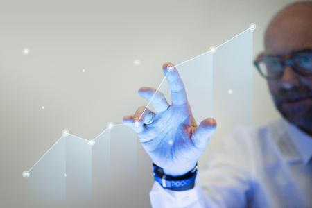 Empresario apuntando con su dedo a un gráfico de crecimiento