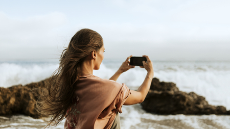 Woman taking photos of the sea