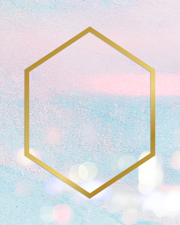 Gold hexagon frame on a pastel pink and blue concrete textured background Banco de Imagens