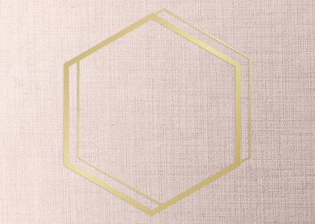 Gold hexagon frame on a peach fabric background Фото со стока