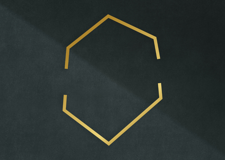 Gold hexagon frame on a dark gray concrete textured background Imagens