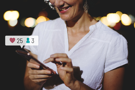 Happy adult woman using her smartphone at a dinner party Imagens