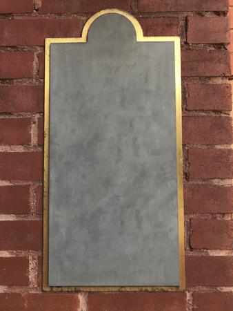 Golden frame against a brick wall