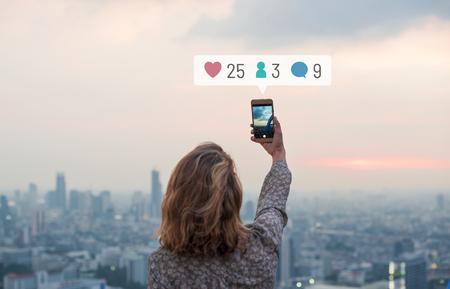 Mujer tomando una foto de la puesta del sol