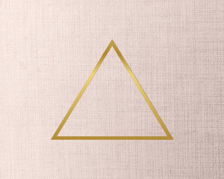 Gold triangle frame on a peach fabric background Фото со стока
