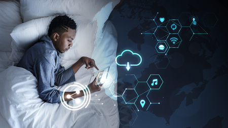 Man using a tablet in bed at night