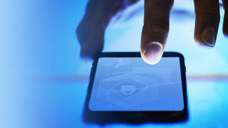 Mann, der seinen Finger auf seinem Telefonbildschirm scannt