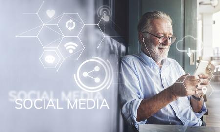 Elderly man watching online movie from his phone Stock fotó