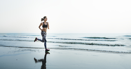 Sporty woman running at the beach Stock Photo