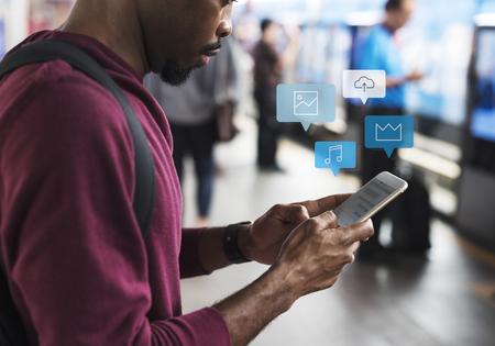 Murzyn korzystający z telefonu komórkowego na platformie