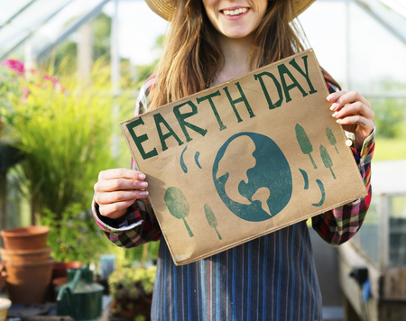 Young woman showing Earth Day poster