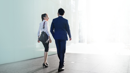 Asian business couple talking while walking