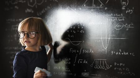 Little genius solving algebra in class Banco de Imagens