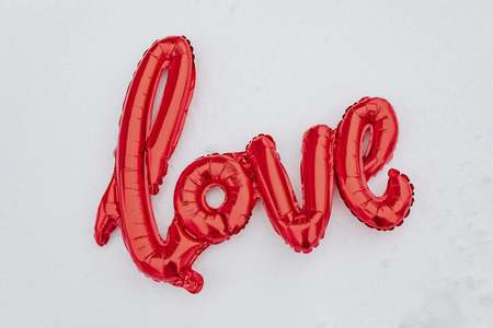 Red love balloon word on a snowy ground Stock Photo