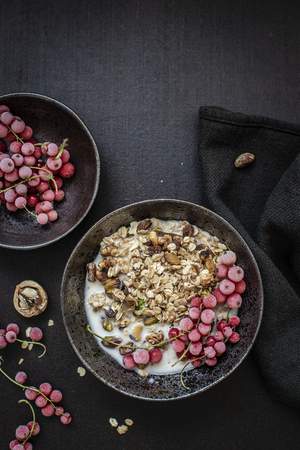 Granola served with soy milk and red currants