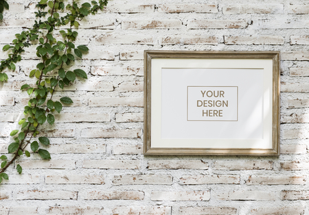 Minimal wooden picture frame on a faded brick wall
