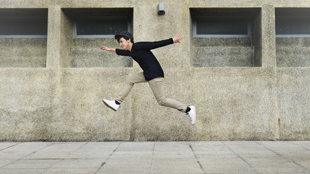 Boy jumping in mid-air on the street