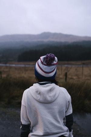 Woman walking on a road in Glen Etive, Scotland Imagens