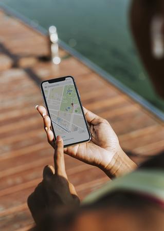 Sportieve vrouw die haar telefoon in een park gebruikt