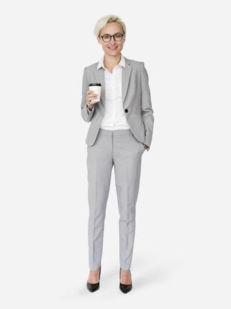 Fröhliche Geschäftsfrau, die einen Kaffeetassenmodellcharakter lokalisiert auf einem weißen Hintergrund hält
