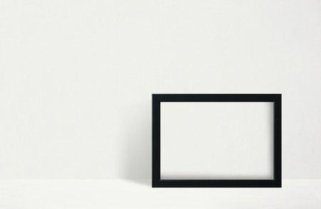 Black frame mockup against a white wall