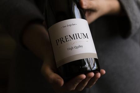 Frau, die eine Flasche Wein mit einem Etikettenmodell hält Standard-Bild