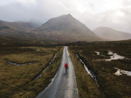 Vrouw die op een weg loopt in Glen Etive, Schotland Stockfoto