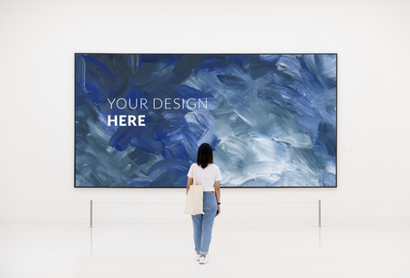 Woman looking at an artwork mockup in an exhibition