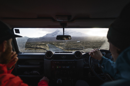 Man driving a car with a friend in the Highlands, Scotland