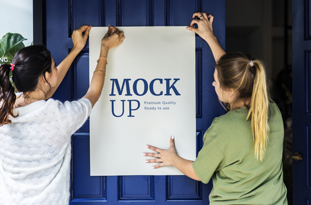 Women putting up a poster mockup