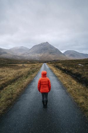 Femme marche sur une route à Glen Etive, Ecosse Banque d'images