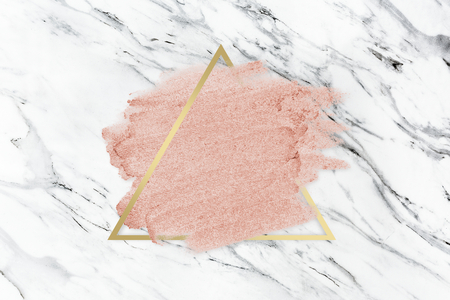 Pastel pink paint with a gold triangle frame on a white marble background Stock fotó